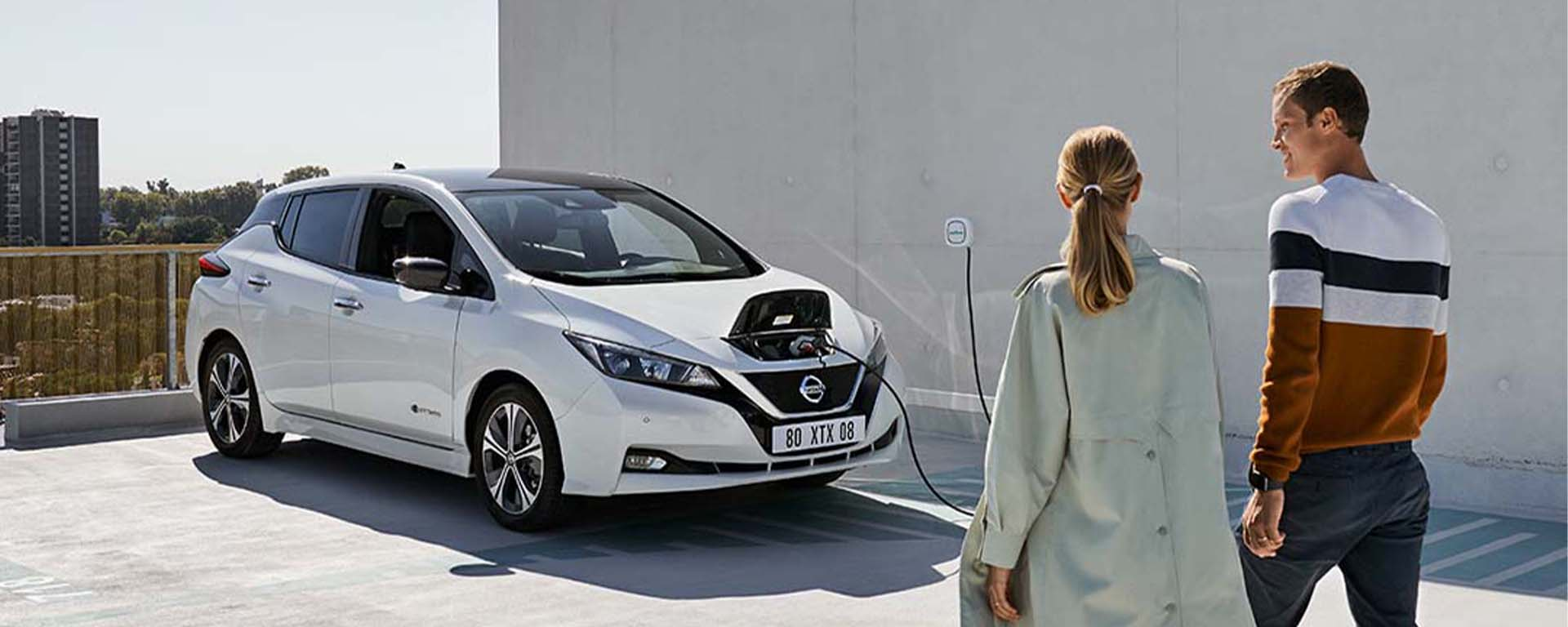 Couple walking towards their new nissan leaf.